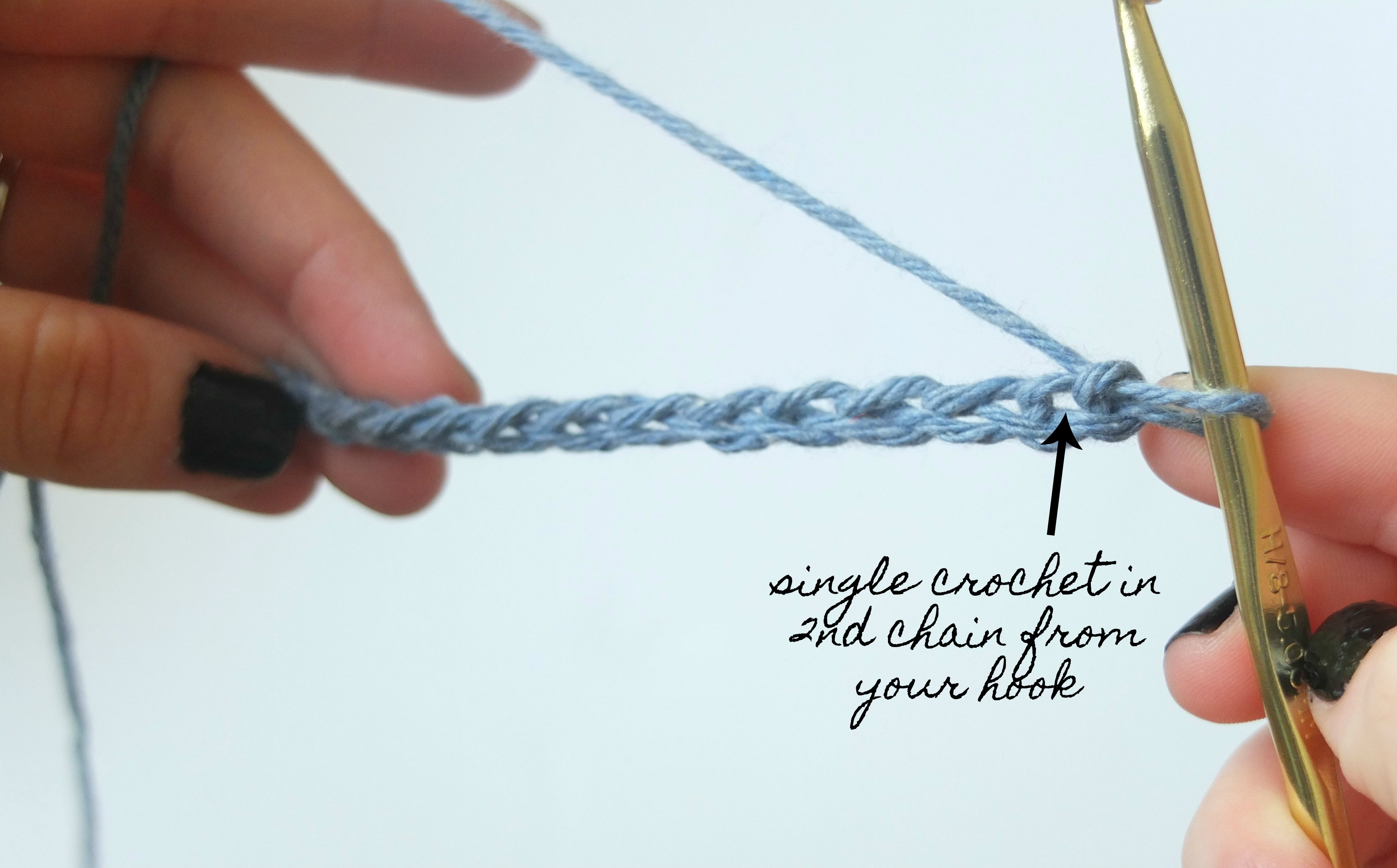 Sigoni is showing how to insert your hook into the second chain from your hook when working the single crochet stitch for beginners