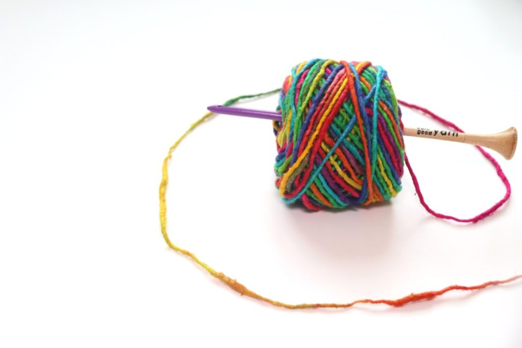 A photo of the rainbow-colored, 100% recycled silk yarn from the Budget-Friendly Crochet Subscription Box Darn Good Yarn of the Month