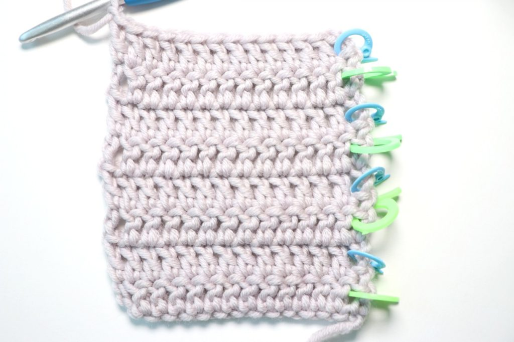 In this photo, Sigoni Macaroni is explaining how you should be counting your crochet stitches and rows using a swatch of double crochet. Pictured is a yarn swatch consisting of eight rows of double crochet stitches. There are stitch markers showing the alternate rows and arrows to mark where each row begins.