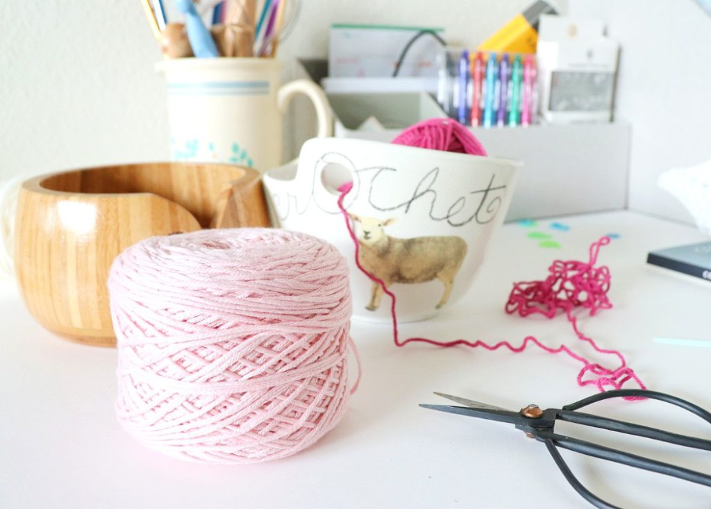 A photo of a skein of yarn wound up into a yarn cake using a ball winder. Using a yarn cake makes it easier to tension your yarn in crochet. Pictured is Lion Brand Yarn Coboo. - via  Sigoni Macaroni's latest blog post, 7 Constructive Tips to Improve Your Yarn Tension