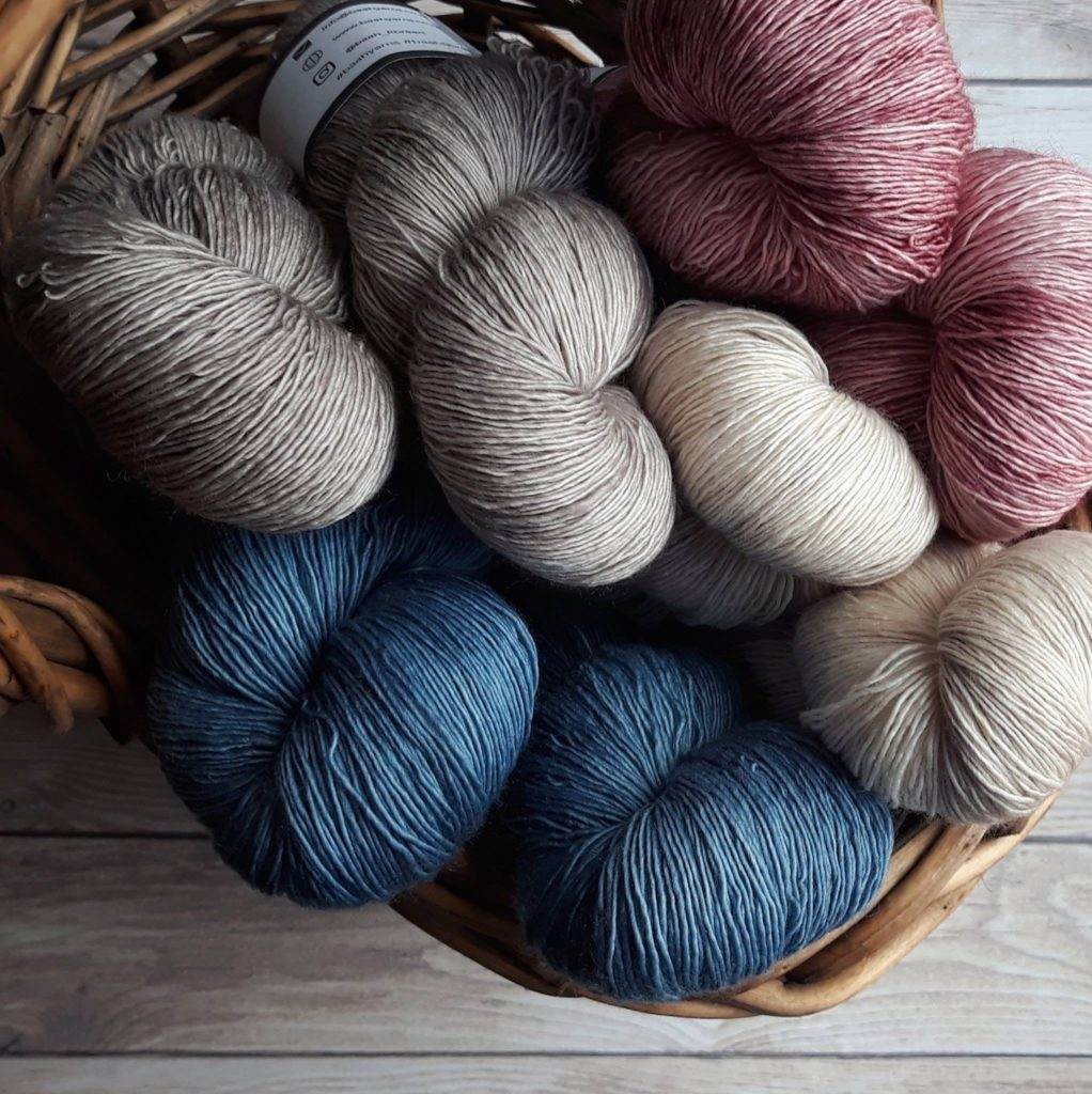 A photo of eight single ply yarn hanks - via Sigoni Macaroni's Yarn Types Explained for Crochet Beginners How to Choose the Right Yarn