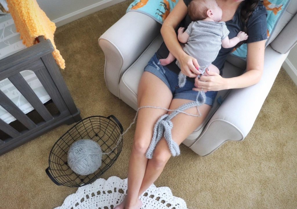 Sigoni crocheting the Cozy Hygge Blanket Wrap in the nursery with her baby boy laying on her chest