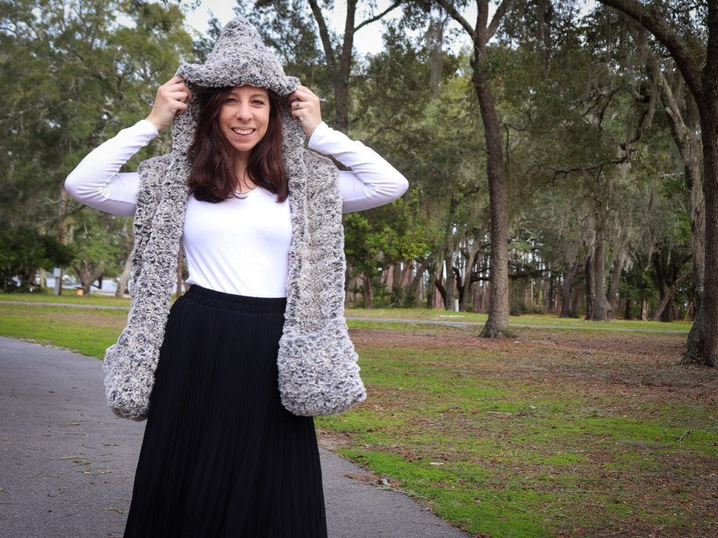 Sigoni is modeling the finished Faux Fur Hooded Scarf with Pockets in a wooded park