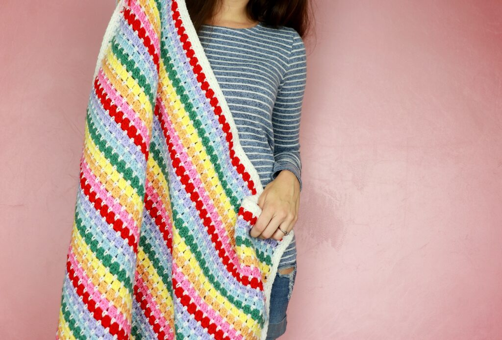 The featured image of Sigoni holding up the striped Rainbow crochet Baby Blanket