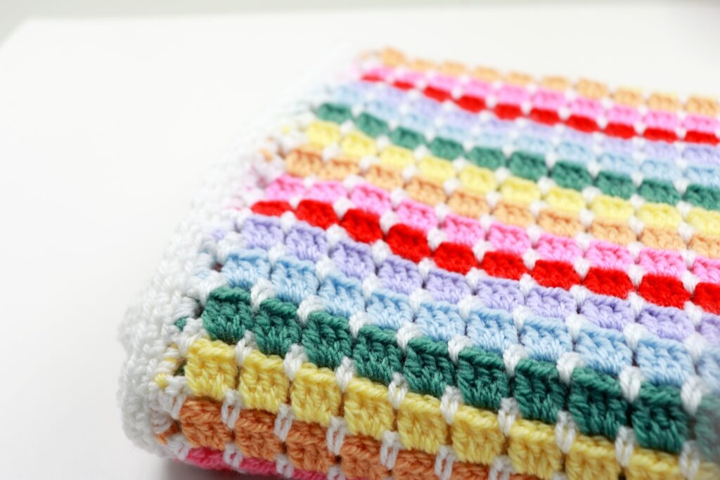 A close up of the block stitch used to create the striped Rainbow Baby Blanket crochet pattern