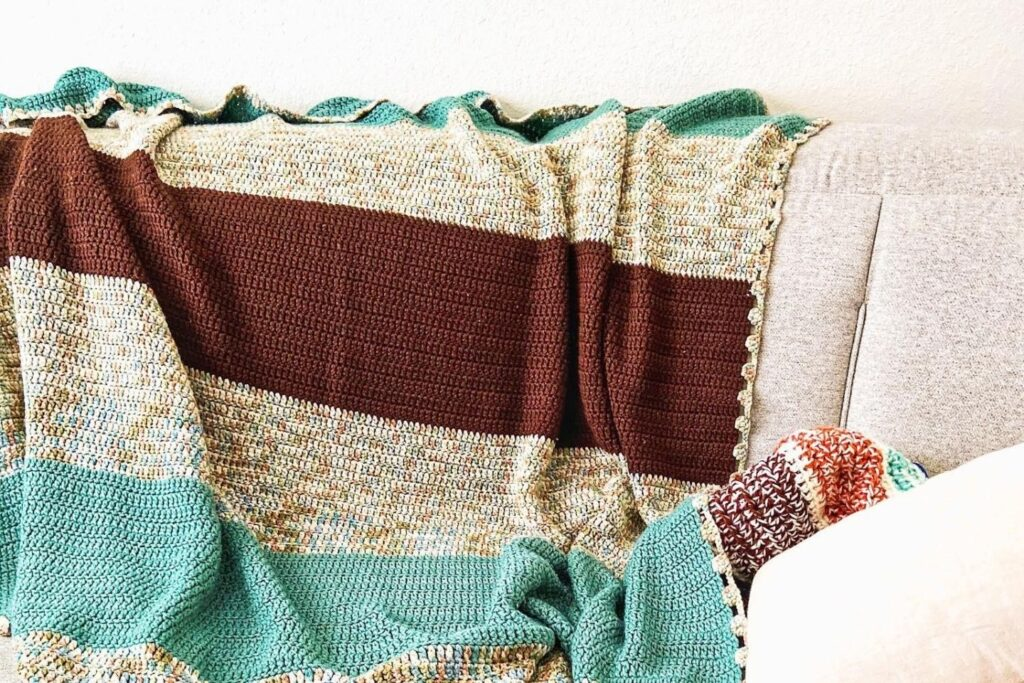 Double crochet Forever Blanket laid over the couch in the colors green, brown, and variegated
