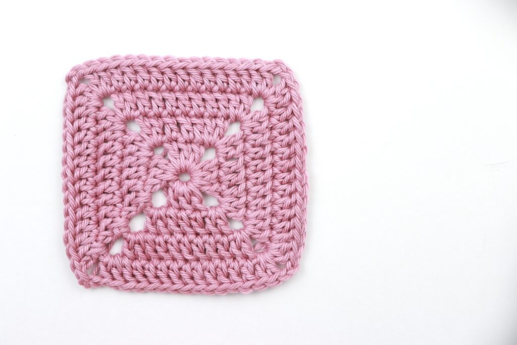 4 rounds of a finished solid granny square in a dark pink color