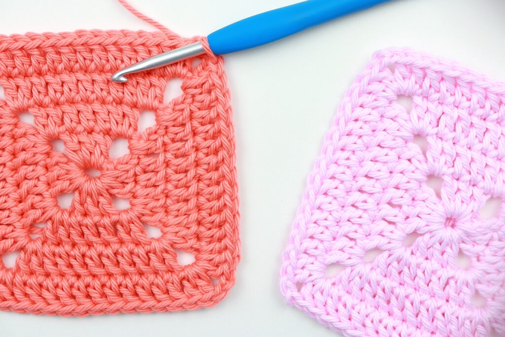 Two finished perfect solid granny squares with 4 rounds. One in orange and the other in pink.