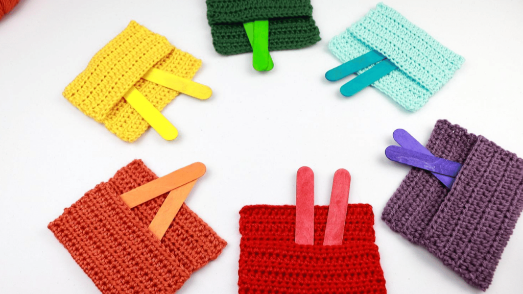 Six Crochet Color Pockets (a quick easy crochet toy for babies) in the colors red, orange, yellow, green, blue, and purple. Each pocket has two colorful popsicle sticks to match.