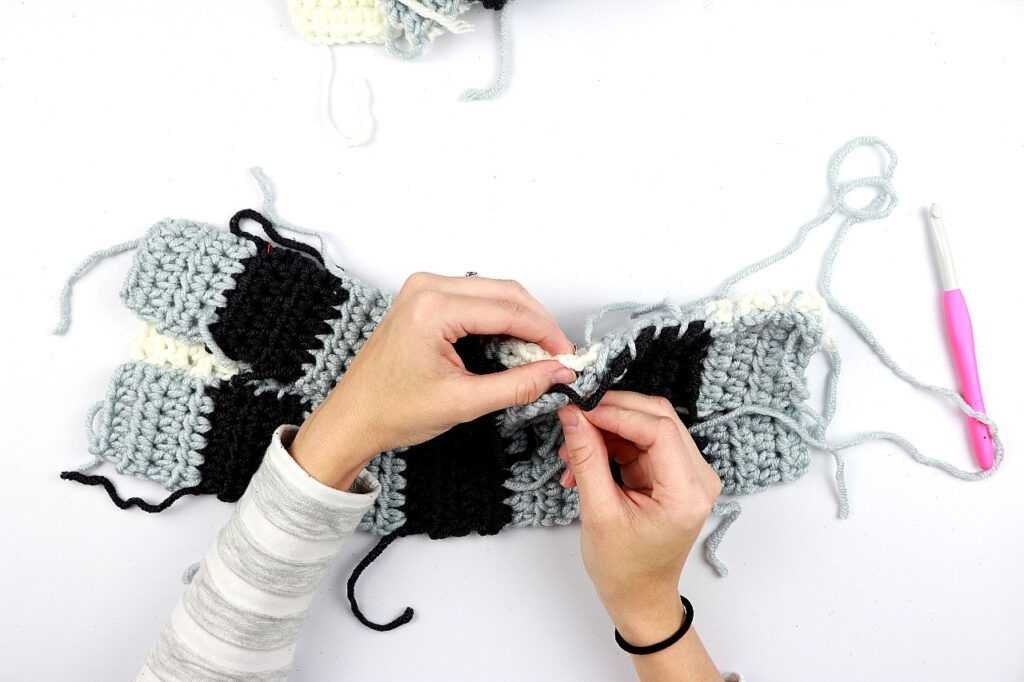 a photo of Sigoni's hands, showing how to sew together the half double crochet panels of the simple gingham style crochet pillow cover.