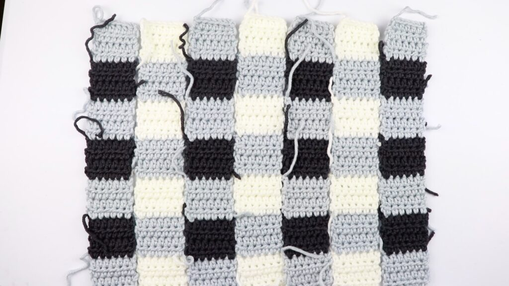 seven half double crochet panels using three different colors (grey, white, and black) of the simple gingham style crochet pillow cover.