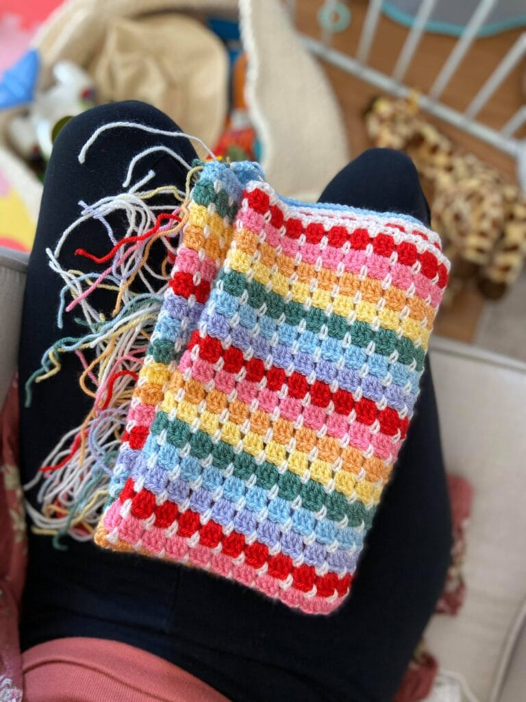 Rainbow crochet baby blanket with hundreds of unwoven ends