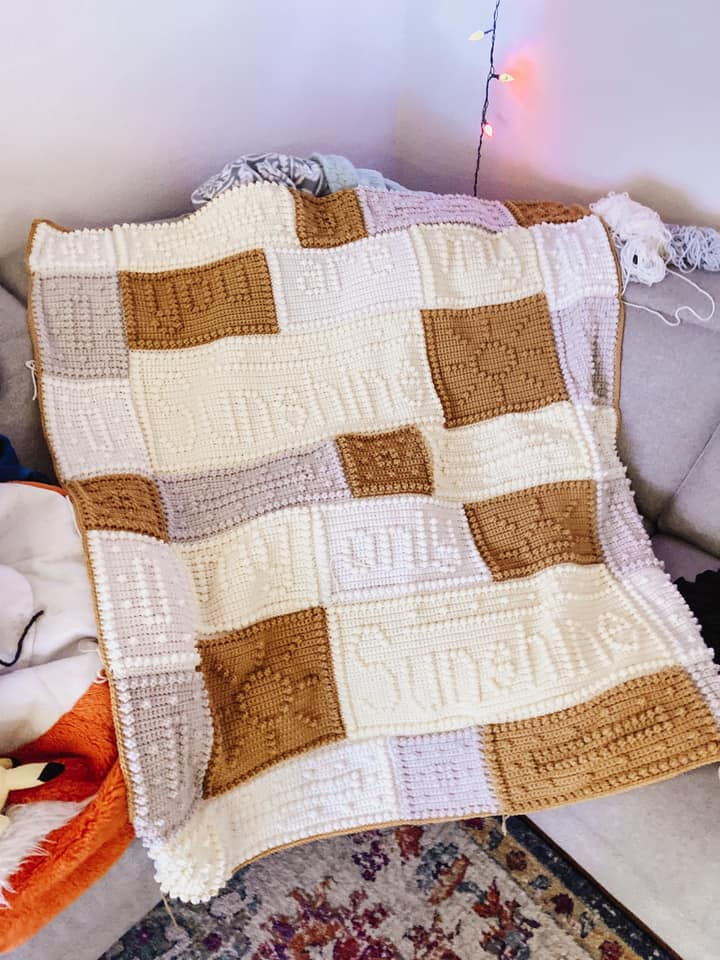 "Crochet blanket in neutral colors that reads ""You are my sunshine."""