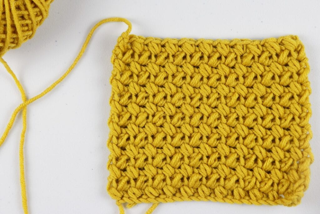 The finished Mini Bean Stitch swatch sample in the color purple using Milla Mia yarn.