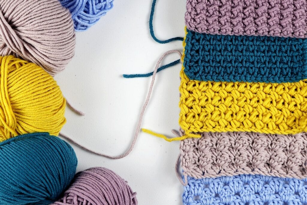 Showing the 5 beginner friendly crochet blanket stitches and the yarn used to make them. The swatches are purple, dark blue, yellow, tan, and light blue