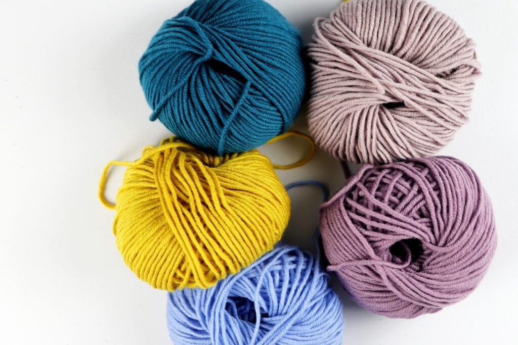 Milla Mia yarn in the colors purple, dark blue, yellow, tan, and light blue
